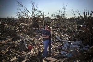 Una coppia guarda sconsolata i resti di una casa di un membro della famiglia il giorno dopo che un tornado ha devastato la città di Moore, Oklahoma.