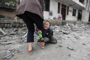 Un bambino stringe  la gamba di sua madre davanti alla loro casa danneggiata dopo un forte terremoto di magnitudo 6.6 al villaggio di Longmen, Lushan County in Ya'an, provincia di Sichuan.