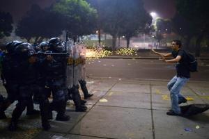 Un manifestante viene colpito da proiettili di gomma della polizia antisommossa dopo gli scontri scoppiati durante una protesta contro la corruzione e gli aumenti dei prezzi a Rio de Janeiro, in Brasile.