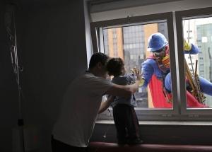 Un uomo vestito come Superman sorride al piccolo paziente Joao Bertola, 2 anni, e a suo padre presso l'Hospital Infantil Sabara a Sao Paulo, Brasile.