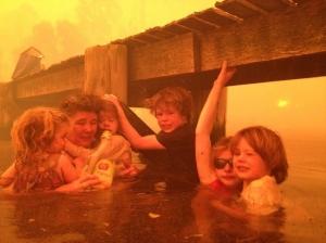 Tammy Holmes e i suoi nipoti si rifugiano sotto un pontile mentre infuriano gli  incendi nella città australiana di Dunalley