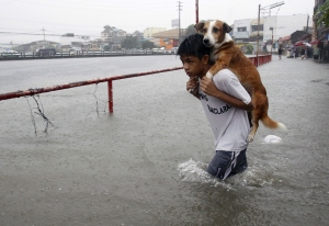 Un ragazzo porta il suo cane sulle spalle a causa dell'acqua portata dalla pioggia a Manila, Filippine