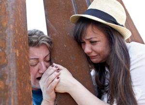 Renata Teodoro, 25 anni, a destra, con la mano tra quella della madre, Gorete Borges Teodoro, attraverso le sbarre di una recinzione di confine a Nogales, in Arizona. la donna era stata deportata sei anni prima dagli Stati Uniti.