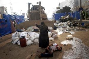 7 Una donna che cerca di fermare un bulldozer militare, a terra c'è una persona ferita dopo gli scontri tra forze di sicurezza e gruppi di opposizione che hanno lasciato centinaia di morti al Cairo.