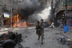 Un uomo pakistano con un bambino in braccio corre lontano dal sito di un autobomba a Peshawar, Pakistan nord-occidentale.