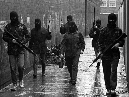 Squadra di volontari dell'IRA si muove attraverso un vicolo di Belfast. Irlanda del Nord, 1980