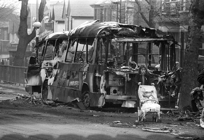 A woman pushes her baby carriage past a burnt bus in West Belfast