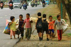 Ragazzi di scuola che passano dai ragazzi che lavorano nelle Filippine