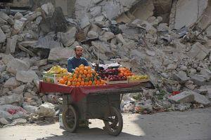 Un venditore di frutta siriano attende per i clienti accanto a un edificio danneggiato il 24 febbraio 2014 nel quartiere Shaar della città settentrionale di Aleppo.