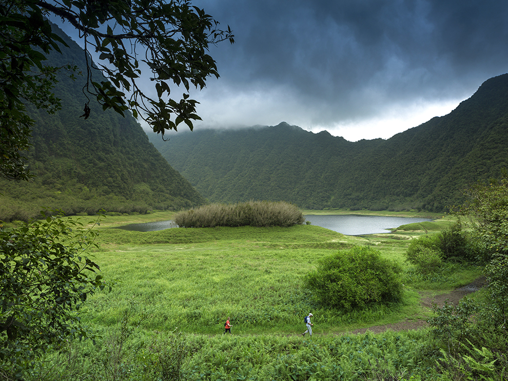 France, Reunion Island, Parc National de la Reunion (National Park of la Reunion), listed as World Heritage by UNESCO, Saint Benoit, Grand Etang, natural landscape of a lake surrounded by mountains under a stormy sky